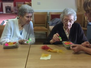 two female residents at Wessex House Care setting participating in a needlefelt workshop